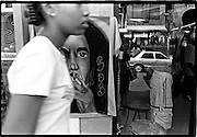 Young girls walks by wall poster of Bob Marley and the Republic Bank window.