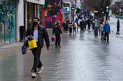 © Licensed to London News Pictures. 21/12/2020. LONDON, UK. A few people are out and about in Oxford Street in the West End as Tier 4, Stay at Home, alert level restrictions are imposed on much of the UK to combat the ongoing coronavirus pandemic in the light of a recently discovered mutant strain that was discovered in the south east of England.  Photo credit: Stephen Chung/LNP