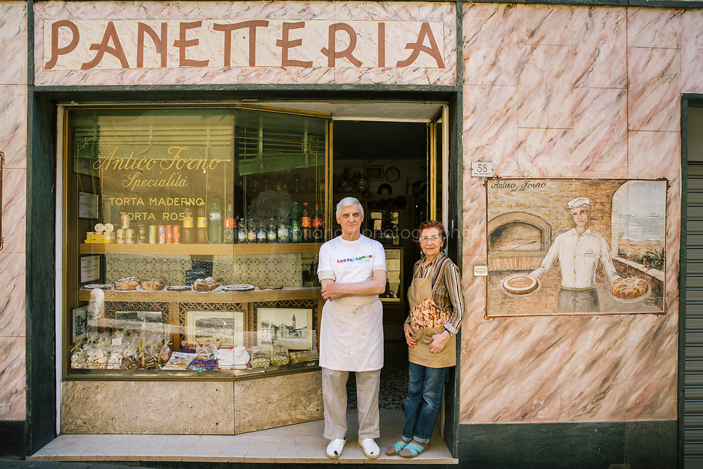 TOSCOLANO MADERNO, ITALY - 19 APRIL 2018: (L-R) Owners Giuseppe and Maria Perolini pose for a portrait in front of their bakery,  Forneria Perolini, in Toscolano Maderno, Italy, on April 19th 2018.<br /> <br /> Lake Garda is the largest lake in Italy. It is a popular holiday location located in northern Italy, about halfway between Brescia and Verona, and between Venice and Milan on the edge of the Dolomites. The lake and its shoreline are divided between the provinces of Verona (to the south-east), Brescia (south-west), and Trentino (north).
