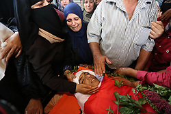 October 4, 2018 - Beit Lahia, Gaza Strip - Relatives of Palestinian Ahmed Abu Habel, 15, who was shot dead by Israeli troops during clashes in a demonstration against Israeli blockade on Gaza Strip, and the United States decision to stop funding and backing the United Nations agency for Palestinian refugees (UNRWA), at the Erez crossing with Israel, mourn over his body during his funeral in Beit Lahia in the northern Gaza Strip on October 4, 2018  (Credit Image: © Ashraf Amra/APA Images via ZUMA Wire)