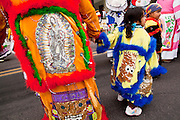 """03 DECEMBER 2011 - PHOENIX, AZ:    Children with sequined Simpson characters on their outfits in a procession to honor the Virgin of Guadalupe in Phoenix Saturday. The Phoenix diocese of the Roman Catholic Church held its Sixth Annual Honor Your Mother Day Saturday to honor the Virgin of Guadalupe. According to Mexican Catholic tradition, on December 9, 1531 Juan Diego, an indigenous peasant, had a vision of a young woman while he was on a hill in the Tepeyac desert, near Mexico City. The woman told him to build a church exactly on the spot where they were standing. He told the local bishop, who asked for some proof. He went back and had the vision again. He told the lady that the bishop wanted proof, and she said """"Bring the roses behind you."""" Turning to look, he found a rose bush growing behind him. He cut the roses, placed them in his poncho and returned to the bishop, saying he had brought proof. When he opened his poncho, instead of roses, there was an image of the young lady in the vision. The Virgin is now honored on Dec 12 in Catholic churches throughout Latin America and in Hispanic communitied in the US.  PHOTO BY JACK KURTZ"""