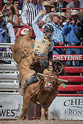 Bull rider Cain Smith of Pendleton, Oregon emerges from the chute on Let R Rip at the Cheyenne Frontier Days rodeo at Frontier Park Arena July 24, 2015 in Cheyenne, Wyoming. Frontier Days celebrates the cowboy traditions of the west with a rodeo, parade and fair.