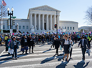 Washington, DC, USA -- March 4, 2020. Wide angle photo of protesters crossing the street  in front of the Supreme Court at an abortion rights rally.