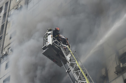March 28, 2019 - Dhaka, Bangladesh - Firefighters try to rescue people trapped in a high-rise building in Dhaka, Bangladesh. At least one person has died and 30 others rushed to hospital as a massive fire engulfed a high-rise building in Bangladesh capital Dhaka's upmarket Banani Thursday afternoon, a hospital official said. (Credit Image: © Salim Reza/Xinhua via ZUMA Wire)