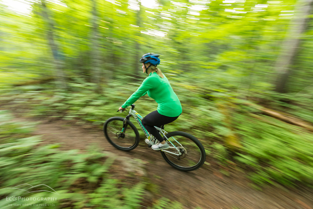 A woman rides her mountain bike on a trail near Deboullie Pond in Aroostook County, Maine. Deboullie Public Reserve Land.
