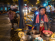 """21 DECEMBER 2015 - BANGKOK, THAILAND: A food vendor with her cart on the street in front of Pak Khlong Talat, also called the Flower Market. The market has been a Bangkok landmark for more than 50 years and is the largest wholesale flower market in Bangkok. A recent renovation resulted in many stalls being closed to make room for chain restaurants to attract tourists. Now Bangkok city officials are threatening to evict sidewalk vendors who line the outside of the market. Evicting the sidewalk vendors is a part of a citywide effort to """"clean up"""" Bangkok.       PHOTO BY JACK KURTZ"""