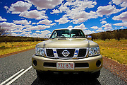 Four-wheel-drive Nissan Patrol vehicle on road in the Red Centre, Australia
