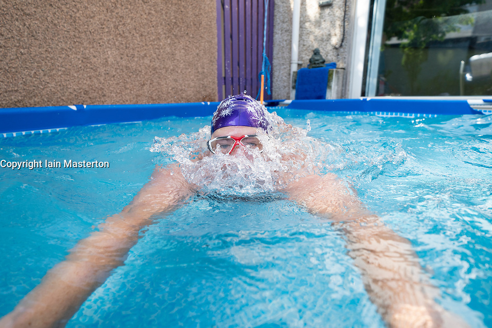 Rosyth, Scotland, UK. 20 May 2020. Jenny Waring (41) from Rosyth, Fife, a wild open water swimmer with the Fife Wild Swimmers group, during a daily dip in her garden pool. Many wild swimmers have been denied the opportunity to pursue their sport during Covid-19 lockdown and have purchased pools for their gardens to maintain their wellbeing. Iain Masterton/Alamy Live News