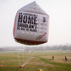 © Licensed to London News Pictures. 17/03/2015. Parliament Hill, Hampstead Heath, UK. Photo call for a giant inflatable house to mark the Homes for Britain housing rally. The rally will see more than 2500 people from over 300 organisations, including private developers, architects, business leaders and homeless charities, gather in Westminster calling on the next government to end the housing crisis within the next 25 years. Photo credit : Stephen Chung/LNP