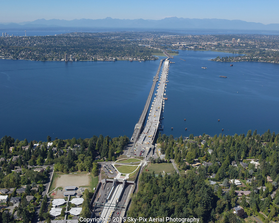 Aerial view of the SR 520 Bridge Replacement project, taken from over Evergreen Point on the east side of Lake Washington, looking toward University of Washington and Montlake, with the City of Seattle and the Olympic Mountains in the background.