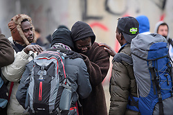 © Licensed to London News Pictures. 24/10/2016. Calais, France. Two migrants cry and embrace each other as they are separated while leaving the camp. The evacuation and demolition begins at the migrant camp in Calais, known as the 'Jungle'. French authorities have given an eviction order to thousands of refugees and migrants living at the makeshift living area of the French coast. Photo credit: Ben Cawthra/LNP