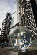 Distorted faces of a couple seen through Petroc Sesti's art instillation called Time Fold in Great Helen's Square, in the City of London. Tall buildings on the right are being constructed and the Lloyds of London building is on the left, its modernity rising high above the capital's cityscape. Petroc Sesti is a London based British artist and Time Fold bends light like a prism, hypnotising the viewer by reflecting on its ever-changing spiral motion.