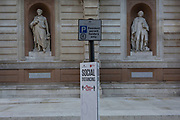 With a further 154 covid deaths reported in the last 24hrs, bringing the total to 43,081 in the UK during the Coronavirus pandemic, a social distance notice has been attached to a parking sign pole outside the rear entrance of the Royal Academy in Burlington Gardens, whose statues to Georges Cuvier and Carl Linnaeus appear to be practicing correct lockdown rules, on 24th June 2020, in London, England.
