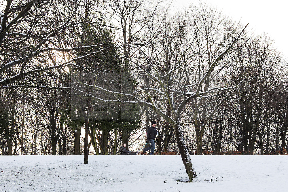 © Licensed to London News Pictures . 26/01/2013 . Salford , UK . A man pulls a child on a sled through the fresh snow . People enjoy fresh overnight snow this morning (26th January 2013) in Buile Hill Park , Salford . Photo credit : Joel Goodman/LNP