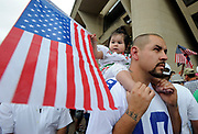 Eli Gutierrez listens to speakers as he holds his one year old daughter Elena in front of Dallas City Hall during the MegaMarch for Immigration Reform,  May 01, 2010
