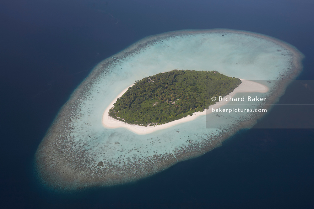 An aerial view of a completely uninhabited, deserted island seen from a regional aircraft passing overhead atolls and islands, an hour's flying time north of Malé, capital of the Indian Ocean Republic of the Maldives. We see the perfectly clear blue sea surrounding a tiny flat island of white coral beach sand, ringing tropical vegetation and scrub that is in jeopardy to rising sea levels as global warming makes sea level locations like this vulnerable to flooding. The Maldives comprise of twenty-six atolls, featuring 1,192 coral islands of which 80 are holiday resorts with 200 inhabited by indigenous communities. This Islamic nation of 298 sq km (115 sq miles), lie seven hundred kilometres (435 miles) south-west of Sri Lanka..
