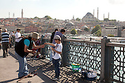 Fisherman on The Galata Bridge which spans the Golden Horn in Istanbul, Turkey...Istanbul 7 June 2012
