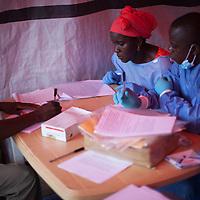 Nene Aminata Diallo (l) and Gamou Saiman Gaston (r), carefully go through the consent process with a participant in the Ebola vaccine trial.