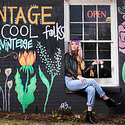 Amanda Braun sits in a window sill with a mural she painted at Alex & Afton Vintedge in Tyler, Texas. Murals have been recently added to the local business and public places in the city. Nathan Lambrecht/Journal Communications