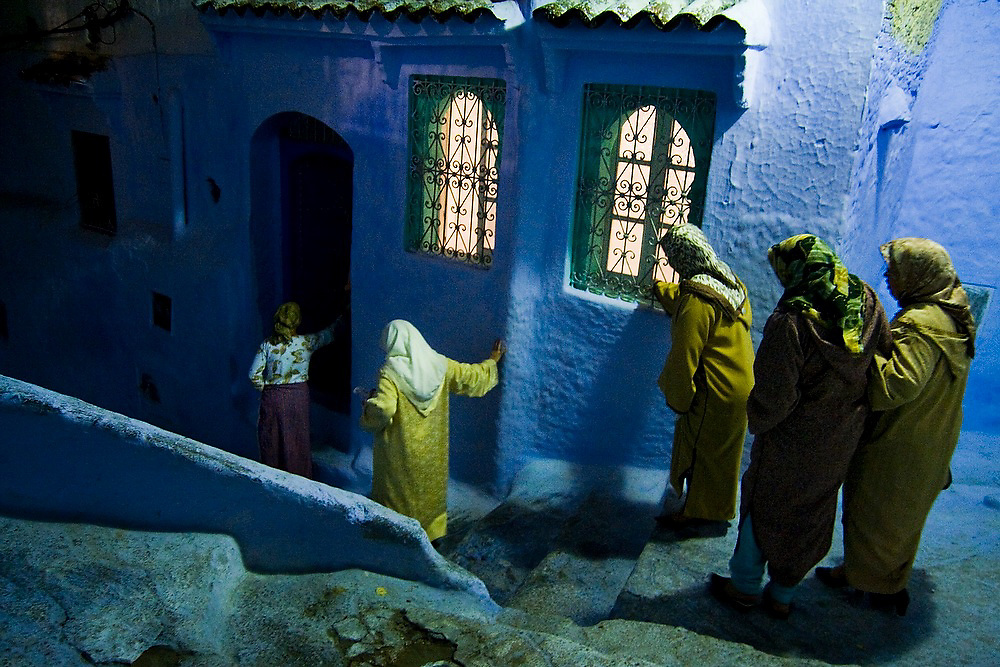 A group of veiled tourist women from Marrakech carefully walk down the steep and uneven stairs with their high heels in a dark alley in the Chefchaouen medina, Morocco.