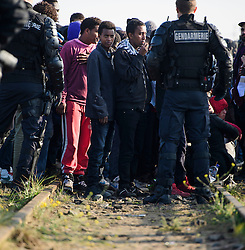 © Licensed to London News Pictures. 25/10/2016. Calais, France.  Hundreds of young, unaccompanied migrants, hoping to go to the UK, wait along disused train tracks, to be processed, before leave the migrant camp in Calais, known as the 'Jungle'. French authorities have moved thousands of refugees and migrants living at the makeshift living area on the French coast, with some still refusing to leave. . Photo credit: Ben Cawthra/LNP