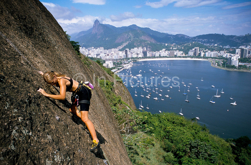 Monica Prazl, rock climbing up the Sugar Loaf mountain with views of the Corcovado (Christ), Botafogo bay and beach and the Yacht club. Climbing is a popular activity amongst the middle classes.