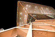 A wall of diamond shaped-windows at the Seattle Central Public Library glow at night in downtown Seattle, Washington, USA