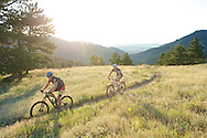 Noel Bennett (left) and David Weber (right) mountain bike the Betasso Link Trail during the sunrise hours at Betasso Preserve just above the town of Boulder, CO. © Brett Wilhelm