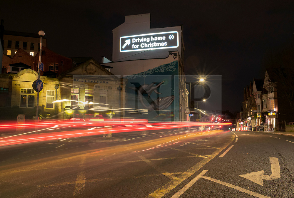 """© Licensed to London News Pictures; 09/12/2020; Bristol, UK. Car light trails created by a long camera exposure are seen as the words """"Driving Home for Christmas"""" are projected onto a building on Park Row in Bristol during the Covid-19 coronavirus pandemic in England. With England under a three-tier system advising against travel it is expected that there will be a lot of traffic just before Christmas when Covid restrictions are lifted and people can travel to visit friends and relations for Christmas. The projection is part of a series for """"Bristol ADVENTures"""", a new arts project spearheaded by Bristol City Centre BID. This sees a new building lit each day with a selection of the most jolly and iconic Christmas lyrics, with a trail of 24 locations complete by Christmas Eve. Photo credit: Simon Chapman/LNP."""