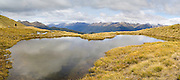Panoramic view of the Mount Burns Tarns, Fiordland National Park, Southland, New Zealand, with a boy walking around the tarn