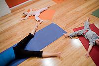 """8 Novembre, 2008. Brooklyn, New York.<br /> <br /> Brigid Preston (in alto), 4 anni, e Mikel Mangoven, 3 anni, seguono un corso di yoga per famiglia con l'istruttrice Ute Kirchgaessner (sinistra) al Bend & Bloom Yoga a Park Slope, Brooklyn, NY. Park Slope, spesso definito dai newyorkesi come """"The Slope"""", è un quartiere nella zona ovest di Brooklyn, New York, e confinante con Prospect Park.  Park Slope è un quartiere benestante che ha il maggior numero di nascite, la qualità della vita più alta e principalmente abitato da una classe media di razza bianca. Per questi motivi molte giovani coppie e famiglie decidono di trasferirsi dalle altre municipalità di New York a Park Slope. Dal punto di vista architettonico, il quartiere è caratterizzato dai brownstones, un tipo di costruzione molto frequente a New York, e da Prospect Park.<br /> <br /> ©2008 Gianni Cipriano for The New York Times<br /> cell. +1 646 465 2168 (USA)<br /> cell. +1 328 567 7923 (Italy)<br /> gianni@giannicipriano.com<br /> www.giannicipriano.com"""