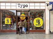 Sale at Typo store in city centre High Street shop, Exeter, Devon, England, UK - two people entering doorway