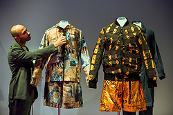 """© Licensed to London News Pictures. 17/10/2019. LONDON, UK. A staff member views """"Mars clothing, SS20 New Horizons collection"""", by Raeburn. Preview of """"Moving to Mars"""" at the Design Museum. The exhibition explores how sending humans to Mars is a frontier for science as well as design and features over 200 exhibits from NASA, the European Space Agency together with new commissions.  The show is open 18 October to 23 February 2020.  Photo credit: Stephen Chung/LNP"""