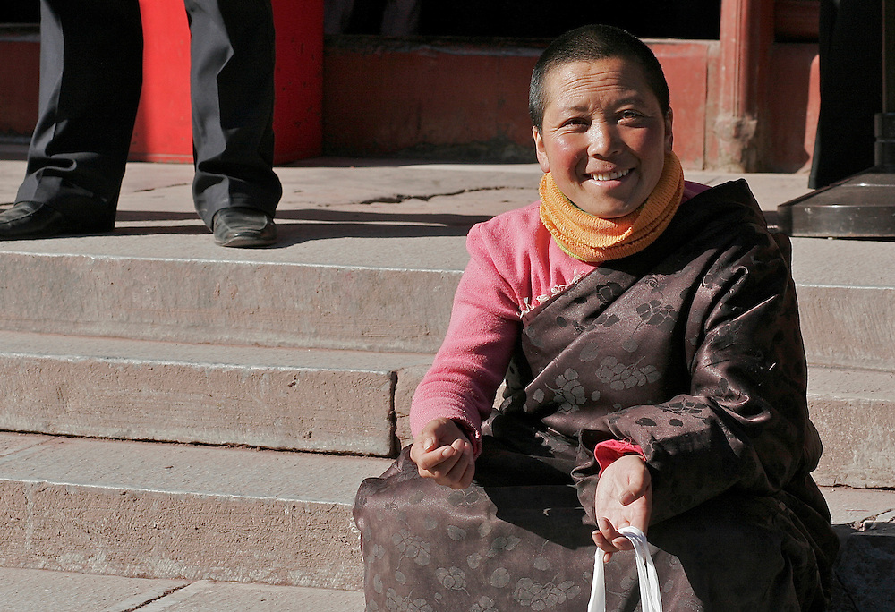 Smiling on the steps of the final hall in Yonghegong a western Chinese woman relaxes in the cool March sun.  This Tibetan Temple is known to tourists as Lama Temple and it's located in Dongcheng District Beijing, China. This is the largest Temple of its kind outside of Tibet.  In 1723 the structure was turned into a Temple after the resident became the third Qing Emperor.