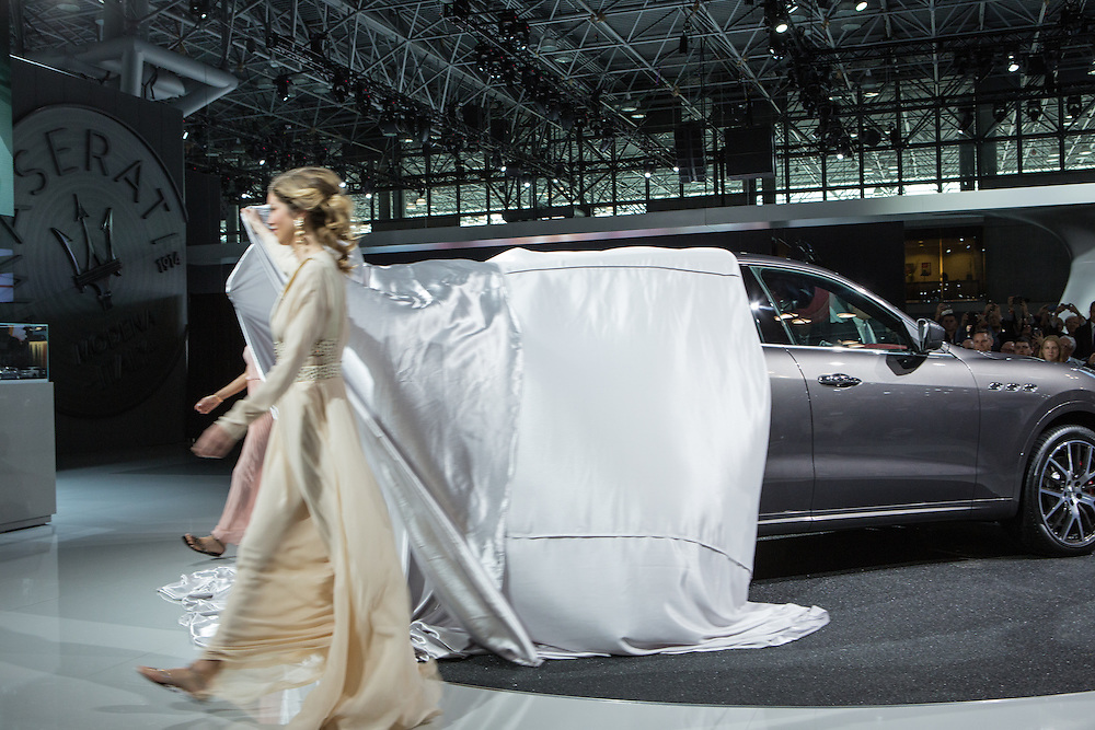 New York, NY, USA-23 March 2016. Two models unveil a Maserati Levante, the automaker's first foray into the luxury SUV market. The car starts at $72,000 US, and is off-road capable.