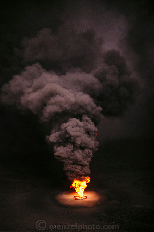 Aerial of burning a burning oil well in the Magwa oil field in Kuwait after the end of the Gulf War in May of 1991. More than 700 wells were set ablaze by retreating Iraqi troops creating the largest man-made environmental disaster in history.