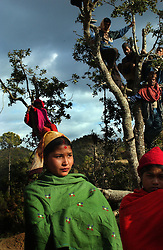 Villagers watch as Maoists perform a traditional dance with Communist flags during  a cultural program where over 1000 people came from several kilometers walking distance in the village of Tila, district of Rolpa, Nepal March 14, 2005. The Maoists have these cultural programs several times every month as a way to educate villagers about their plans and programs. (Ami Vitale)
