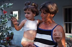 Mother standing outside house near Soroa; Cuba; holding young daughter,