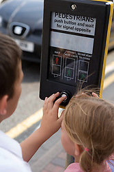 Brother and Sister pressing the button on a pedestrian crossing,