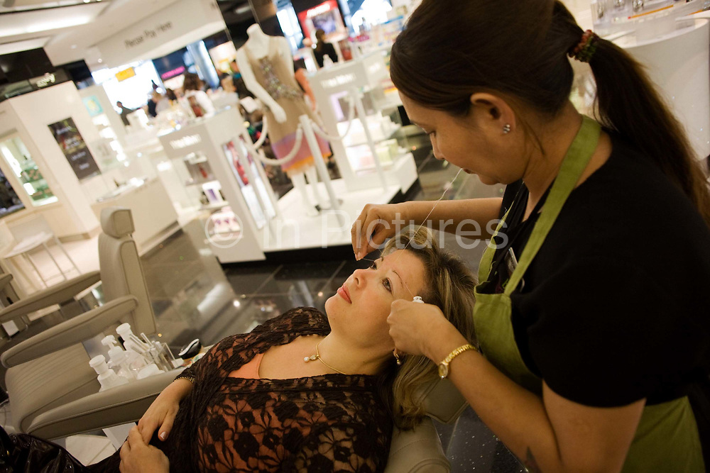"""Lying horizontal in a busy salon, a lady passenger receives eyebrow threading treatment during a beauty session at the Blink Eyebrow Bar in World Duty Free, Heathrow Airport's terminal 5. The beautician holds the thread that squeezes the woman's eyebrow follicles, removing the tiniest and finest hair right from the root. Threading is a technique that China has been using for centuries but has recently become popular in western countries. Amid the busy departures terminal of this international aviation hub, this is a corner of quiet and tranquillity before the woman traveller boards her business flight after this few minutes of pampering. From writer Alain de Botton's book project """"A Week at the Airport: A Heathrow Diary"""" (2009)."""