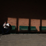 A punter studies form in the later afternoon sunlight at Belmont Park during the Jockey Club Gold Cup Day, Belmont Park, New York. USA. 28th September 2013. Photo Tim Clayton