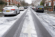 Looking uphill, an urban landscape scene of a light dusting of snow that has covered the road surface of a residential street in Herne Hill, SE24, Lambeth, south London where cars are parked on both sides outside their owners' houses, on 8th February 2021, in London, England.