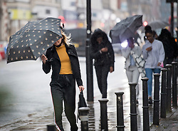 © Licensed to London News Pictures. 05/10/2020. London, UK. Members of the public attempt to shelter form a downpour of rain on Kilburn High Road in North London. Photo credit: Ben Cawthra/LNP