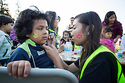 Eddie Arteaga, 5, has his face painted by Vanessa Le, 15, during the 6th Annual District 4 National Night Out Resource Fair and Movie Night at Northwood Park in San Jose, California, on August 6, 2013. (Stan Olszewski/SOSKIphoto)