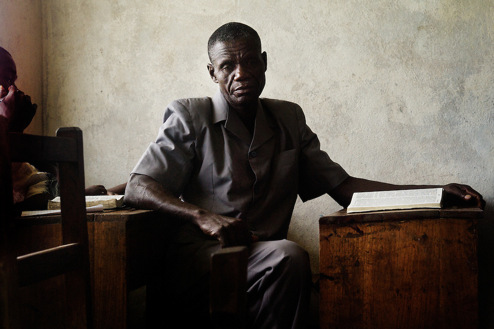 A male Christian reads the Bible while listening to the sermon at a church in Monrovia, Liberia.