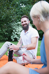 Young man opening wine bottle on picnic with his wife, Bavaria, Germany