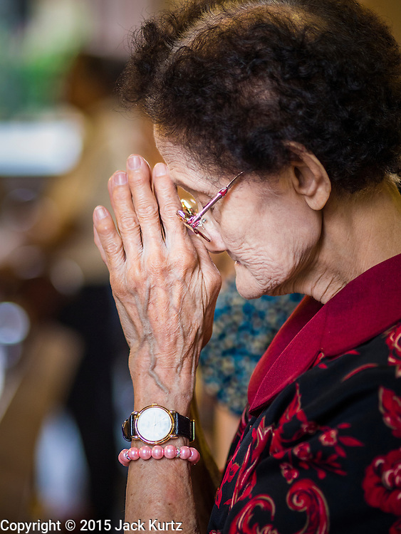 15 FEBRUARY 2015 - BANGKOK, THAILAND: A woman prays during mass in Santa Cruz Catholic Church in the Kudeejeen neighborhood in Bangkok. Santa Cruz church was established in 1770  and is one of the oldest and most historic Catholic churches in Thailand. The church was originally built by Portuguese soldiers allied with King Taksin the Great. Taksin authorized the church as a thanks to the Portuguese who assisted the Siamese during the war with Burma. Most of the Catholics in the neighborhood trace their family roots to the original Portuguese soldiers who married Siamese (Thai) women. There are about 300,000 Catholics in Thailand in about 430 Catholic parishes and about 660 Catholic priests in Thailand. Thais are tolerant of other religions and although Thailand is officially Buddhist, Catholics are allowed to freely practice and people who convert to Catholicism are not discriminated against.      PHOTO BY JACK KURTZ