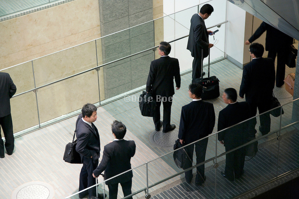businessmen meeting up on a hallway bridge of a large office building