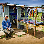 A recipient of UNDP-supported business training sits outside the enterprise he's established, a combined unisex hair salon and accessories store. Giwa Resettlement Farm, near Nakuru in Kenya's Rift Valley Province.