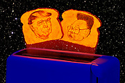 Glowing toast burnt with the faces of Donald Trump and Kim Jong Un pop up from a toaster. Blacklight photography.